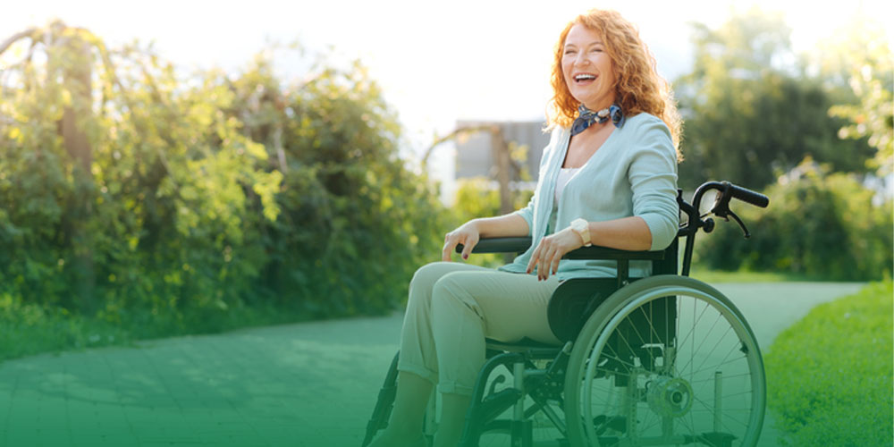 woman smiling in wheelchair outside